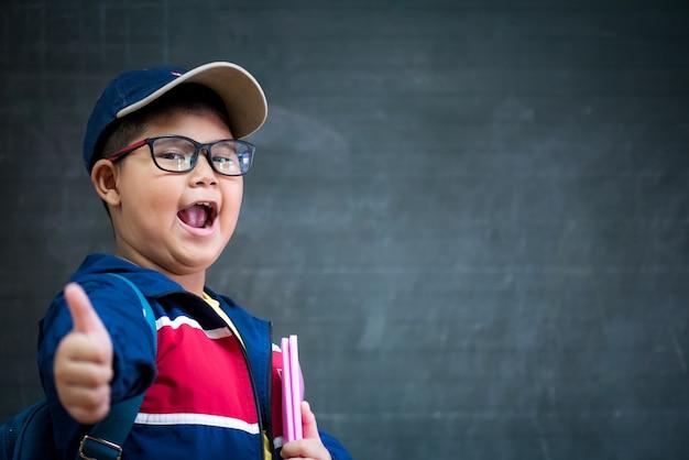Szczęśliwa chłopiec w szkłach z kciukiem up dla z powrotem szkoły pojęcie.