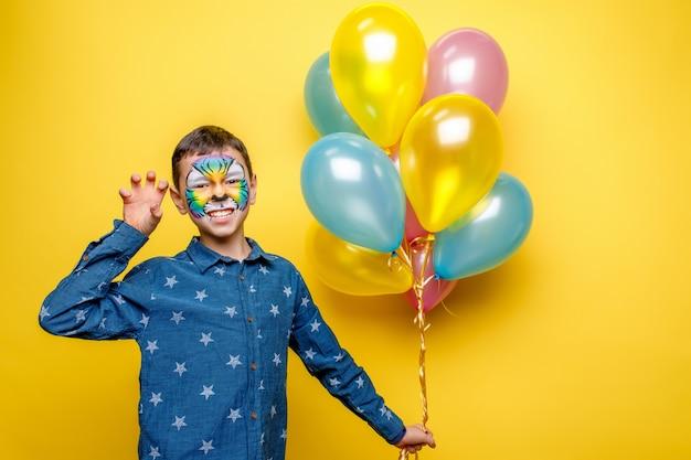 Szczęśliwa chłopiec z aquagrim na przyjęciu urodzinowym, kolorowy tygrys trzyma kolorowych balony odizolowywający na kolorze żółtym