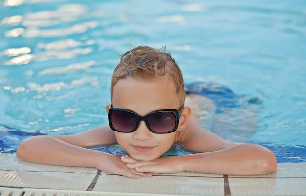 Szczęśliwa chłopiec z blondynu uśmiechniętym obsiadaniem w pływackim basenie
