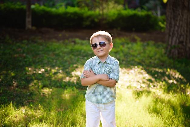 Szczęśliwa chłopiec z okularami przeciwsłonecznymi w ogródzie.