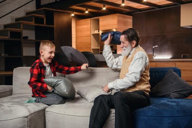 Szczęśliwa chłopiec z śmiesznym nowożytnym dziadunio bojem z poduszkami ma zabawę wpólnie siedzi na wygodnej leżance w domu.