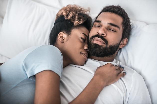 Szczęśliwa chwila. ciemnoskóry, młody dorosły mąż i żona, leżący z zamkniętymi oczami, obejmujący się w domu na łóżku