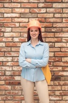 Szczęśliwa chwila. młoda dorosła całkiem szczęśliwa kobieta w kasku ochronnym i w lekkich ubraniach, trzymająca dokumenty stojące na tle ceglanego muru
