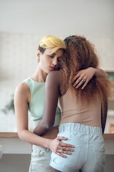 Szczęśliwa chwila. młoda szczęśliwa kobieta z zamkniętymi oczami stoi przytulanie amerykańska kobieta w pokoju