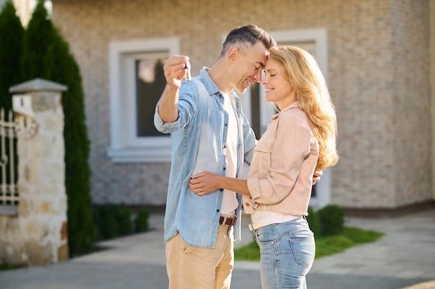 Szczęśliwa chwila. szczęśliwy mężczyzna z kluczem w dłoni i kobieta z długimi blond włosami, dotykająca twarzy z zamkniętymi oczami w pobliżu domu