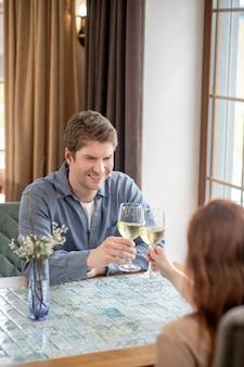 Szczęśliwa chwila. uśmiechnięty atrakcyjny mężczyzna z kieliszkiem białego wina i kobietą naprzeciwko siedzącej w restauracji świętującej wydarzenie