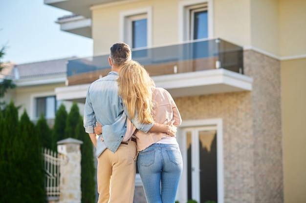 Szczęśliwa chwila. widok z tyłu mężczyzny i długowłosej kobiety w zwykłych ubraniach, patrzących na swój nowy dom w pogodne popołudnie