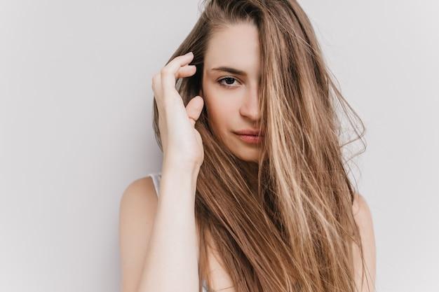 Szczęśliwa ciemnooka dziewczyna pozuje rano. strzał czarujący kaukaski modelka dotykając jej ciemne włosy.
