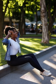 Szczęśliwa ciemnoskóra dziewczyna w parku na spacerze