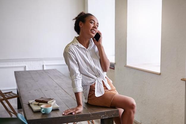 Szczęśliwa ciemnoskóra kobieta robi przerwę od pracy, siedzi na stole i przyjemnie rozmawia przez telefon komórkowy, ubrana w białą koszulę w paski
