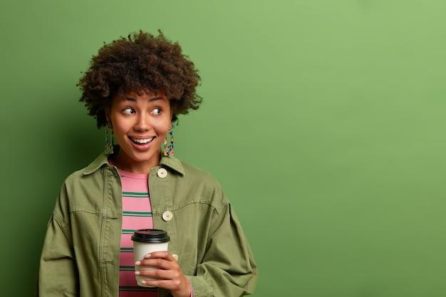 Szczęśliwa ciemnoskóra kobieta trzyma jednorazową filiżankę gorącego napoju, patrzy na bok i uśmiecha się radośnie, robi przerwę na kawę, lubi poranny napój kofeinowy, odizolowany na zielonej ścianie, miejsce na kopię