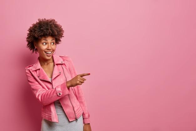 Szczęśliwa ciemnoskóra, kręcona młoda kobieta wskazuje, że z daleka widzi coś niesamowitego, pozytywnie chichoczącego
