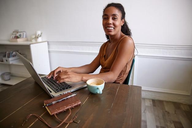 Szczęśliwa ciemnoskóra ładna kobieta pracująca zdalnie ze swoim nowoczesnym laptopem, wyglądająca wesoło i trzymająca ręce na klawiaturze