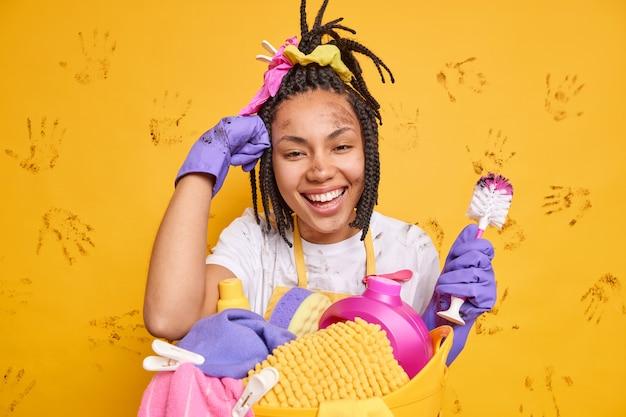 Szczęśliwa ciemnoskóra młoda kobieta z dredami wygląda z radością trzyma narzędzie do czyszczenia pochyla się przy koszu na pranie nosi gumowe lateksowe rękawiczki na białym tle nad żywą żółtą ścianą