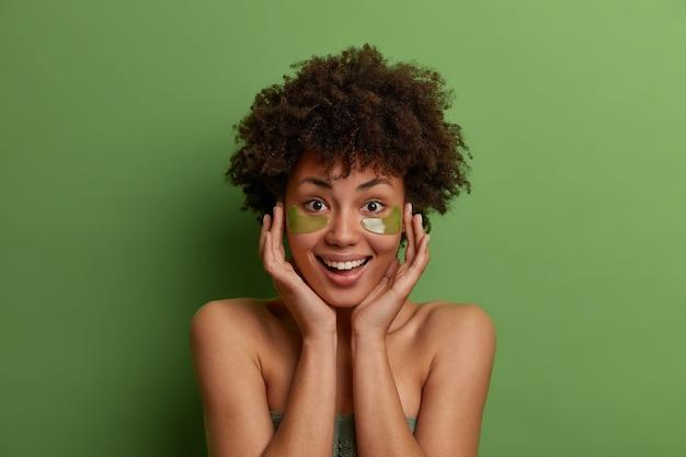 Szczęśliwa ciemnoskóra modelka o świeżym wyglądzie, nakłada przeciwzmarszczkowe zielone hydrożelowe plastry, dotyka miękkiej skóry, radośnie się uśmiecha, modeluje w pomieszczeniach na jasnej, żywej ścianie. uroda, dobre samopoczucie