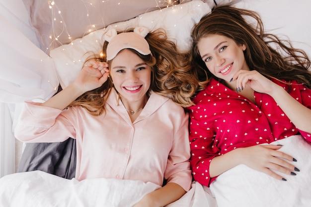 Szczęśliwa ciemnowłosa dziewczyna pozuje z przyjemnością w wygodnym łóżku. urocza blondynka nosi różową piżamę, która chłodzi o poranku.