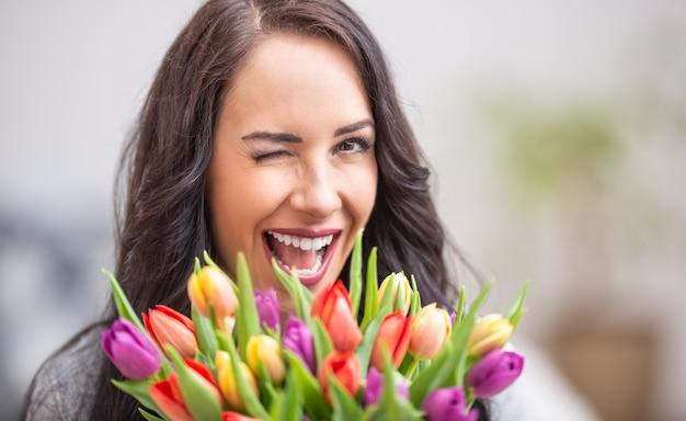 Szczęśliwa ciemnowłosa kobieta mrugająca i trzymająca piękny bukiet pełen tulipanów podczas narodowego dnia kobiet.