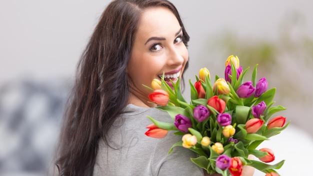 Szczęśliwa ciemnowłosa kobieta szeroko uśmiechnięta i trzymająca piękny bukiet pełen tulipanów podczas narodowego dnia kobiet.