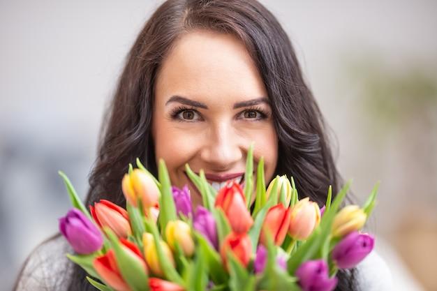 Szczęśliwa ciemnowłosa kobieta trzyma piękny bukiet pełen tulipanów podczas narodowego dnia kobiet.