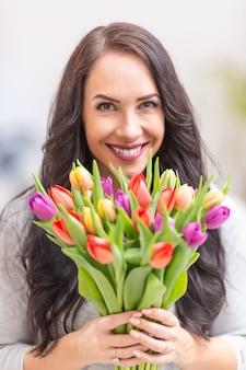 Szczęśliwa ciemnowłosa kobieta trzyma w rękach piękny bukiet pełen tulipanów podczas narodowego dnia kobiet.