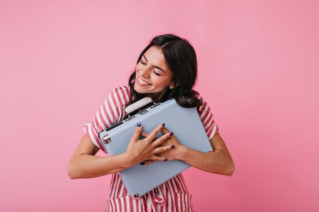 Szczęśliwa ciemnowłosa z radości zamknęła oczy i mocno przytula swoją walizkę. portret modelki w biało-różową tunikę i fioletowy manicure.