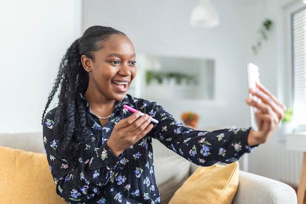 Szczęśliwa, ciężarna afrykanka pokazuje swój test ciążowy i robi selfie podczas wideorozmowy. szczęśliwa kobieta biorąc zdjęcie testu ciążowego z telefonu komórkowego i publikowanie obrazu w mediach społecznościowych.