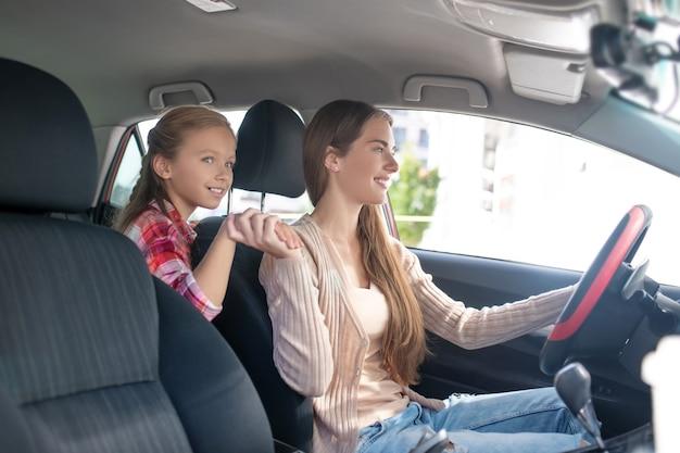 Szczęśliwa córka trzymająca mamę za rękę, prowadząca samochód