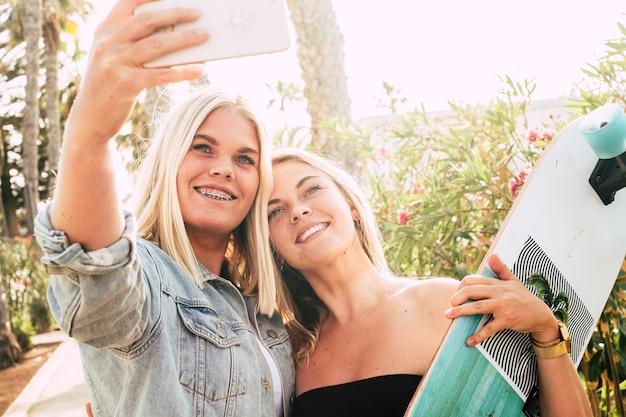 Szczęśliwa coule młodych atrakcyjnych kaukaskich dziewczyn robiących zdjęcie selfie za pomocą nowoczesnego telefonu