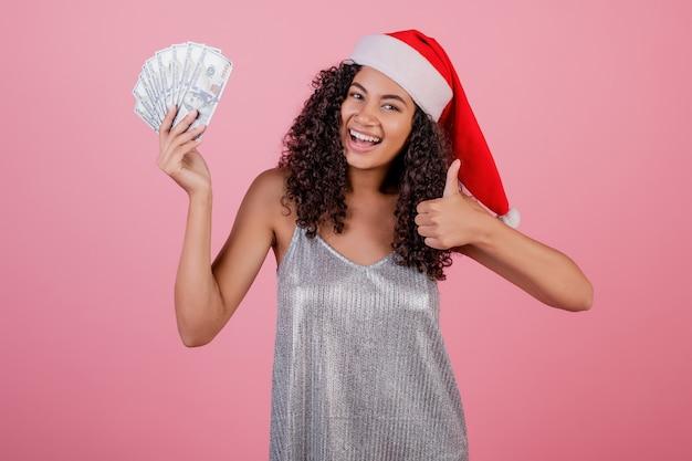 Szczęśliwa czarna dziewczyna trzyma sto dolarowych rachunków jest ubranym santa kapelusz odizolowywający