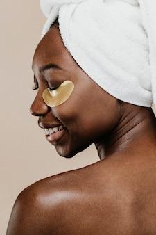 Szczęśliwa czarna kobieta nosząca złotą maskę na oczy