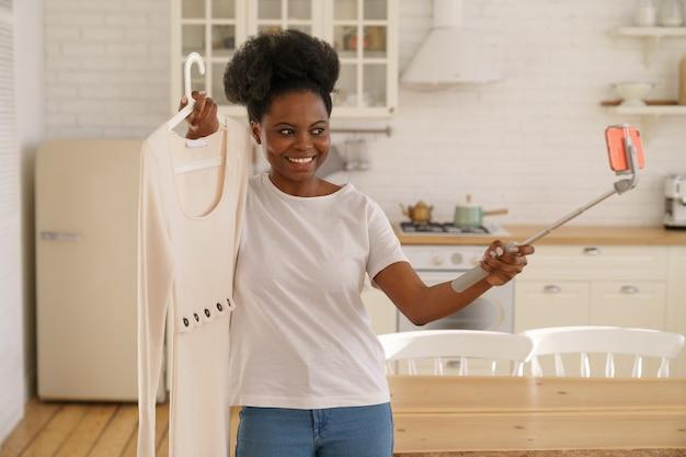 Szczęśliwa czarna kobieta pokazująca letnią sukienkę mody przez smartfona na statywie online w transmisji na żywo
