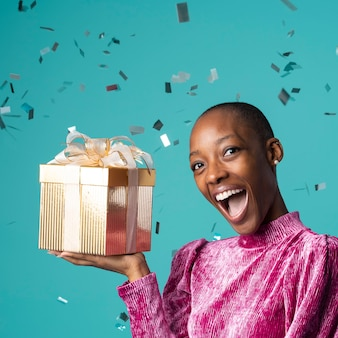 Szczęśliwa czarna kobieta trzyma pudełko na prezent