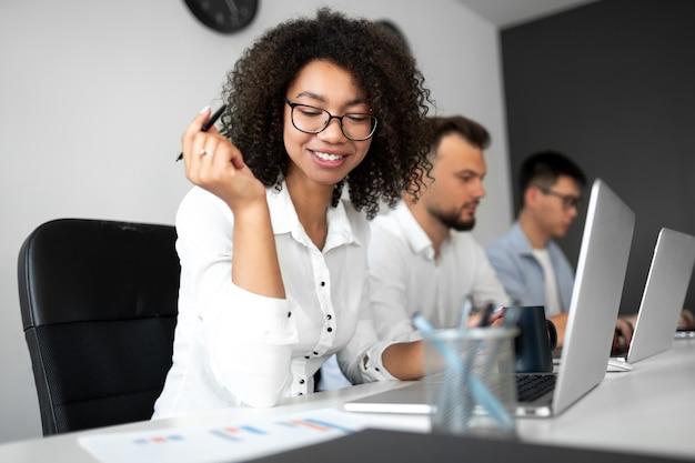 Szczęśliwa czarna kobieta z kręconymi włosami uśmiecha się i odczytuje dane, siedząc przy stole i pracując z międzynarodowym zespołem w firmie informatycznej