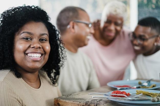 Szczęśliwa czarna młoda kobieta je obiad z rodziną w domu - skup się na twarzy dziewczyny