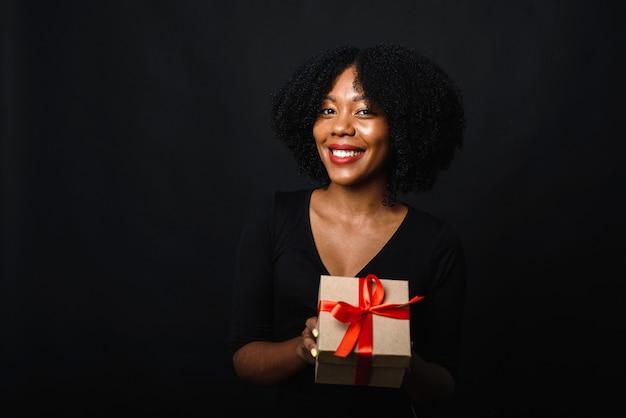 Szczęśliwa czarna młoda kobieta z afro trzyma świąteczny prezent w dłoniach i uśmiecha się. koncepcja dawania prezentów i świątecznych zakupów. czarny piątek.