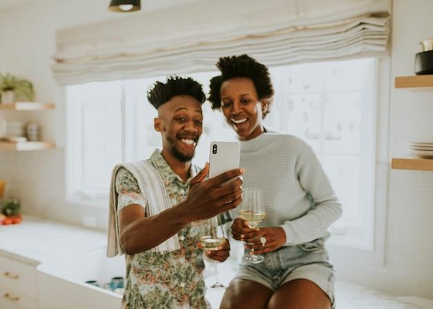 Szczęśliwa czarna para robi selfie w domu za pomocą telefonu komórkowego