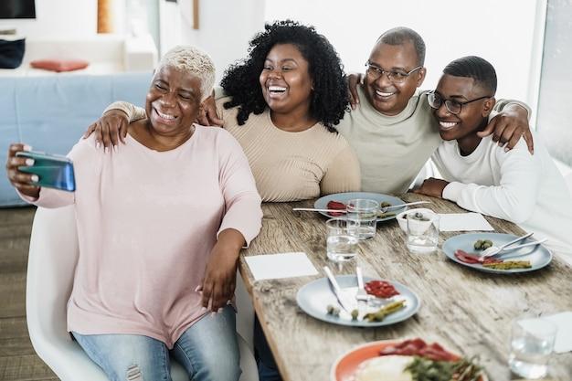 Szczęśliwa czarna rodzina biorąc selfie z telefonu komórkowego w domu