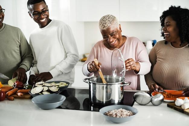 Szczęśliwa czarna rodzina gotuje wegańskie jedzenie w kuchni w domu