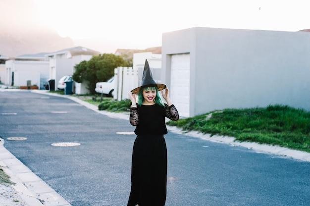 Szczęśliwa czarownica trzyma kapelusz