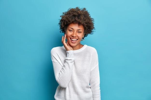 Szczęśliwa czarująca kobieta z kręconymi włosami uśmiecha się szeroko twarz cieszy się miękką skórą ma naturalne piękno wyraża pozytywne emocje ubrana nietypowy sweter odizolowany na niebieskiej ścianie studia