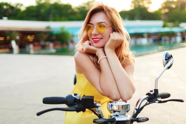 Szczęśliwa czerwona głowa kobieta w żółtej sukience relaksując się na swoim skuterze elektrycznym, spędzając wakacje w nowoczesnym mieście. romantyczny nastrój.