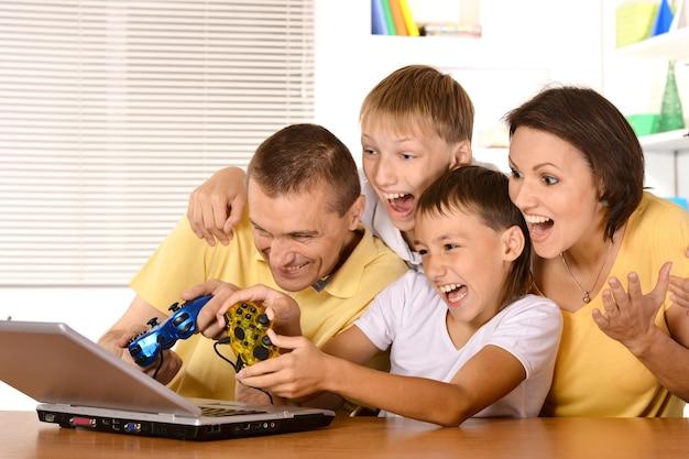 Szczęśliwa czteroosobowa rodzina grająca na laptopie przy stole