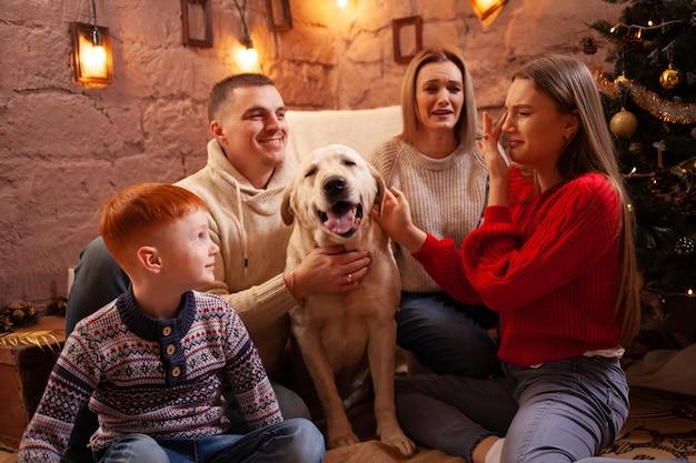 Szczęśliwa czteroosobowa rodzina i pies świętują nowy rok