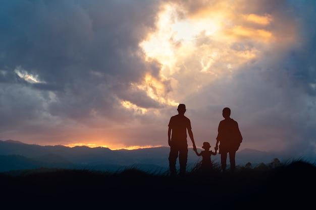 Szczęśliwa czteroosobowa rodzina patrzy na zachód słońca.