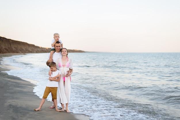 Szczęśliwa czteroosobowa rodzina ściska na dennym wybrzeżu. rodzice, ciężarna matka i dwaj synowie.