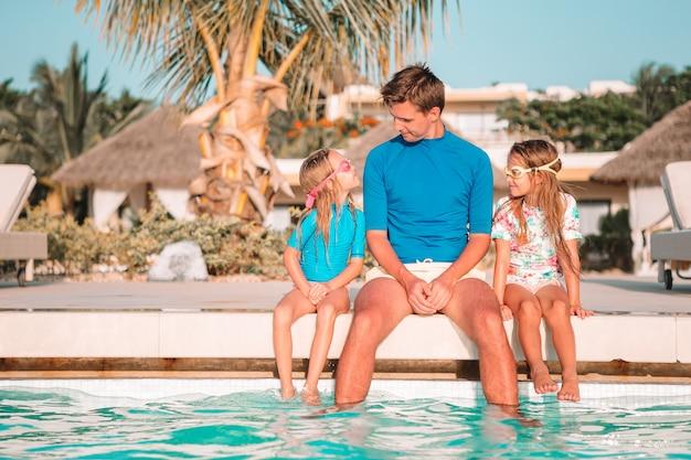 Szczęśliwa czteroosobowa rodzina w basenie na świeżym powietrzu