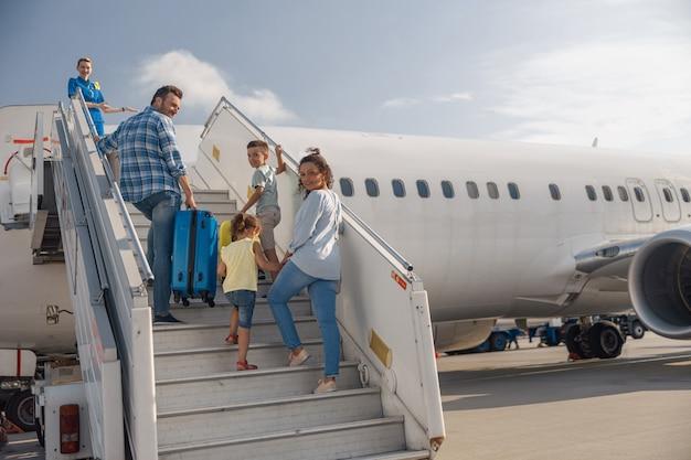 Szczęśliwa czteroosobowa rodzina wsiadająca, wchodząca na pokład samolotu w ciągu dnia, gotowa na letnie wakacje. ludzie, podróże, koncepcja wakacji