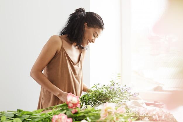 Szczęśliwa czuła afrykańska kobieta ono uśmiecha się robić bukietowi kwiaty przy miejscem pracy nad biel ścianą.