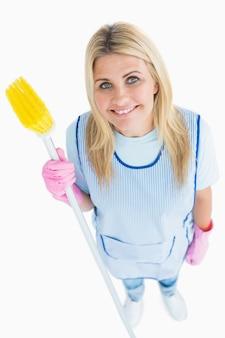 Szczęśliwa czysta kobieta trzyma miotłę