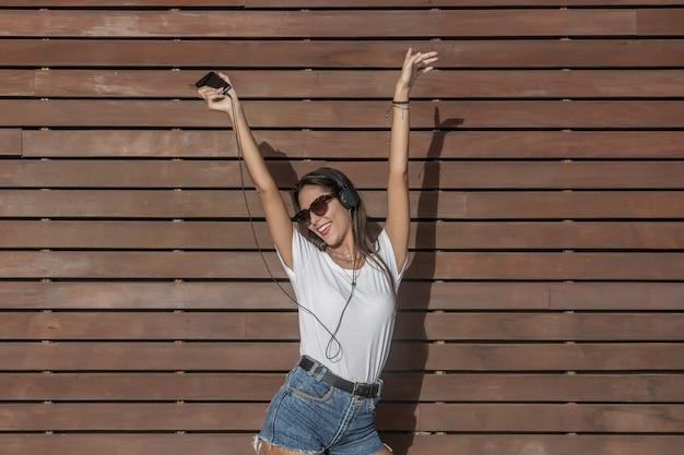 Szczęśliwa dama tańczy i trzyma ręce do góry